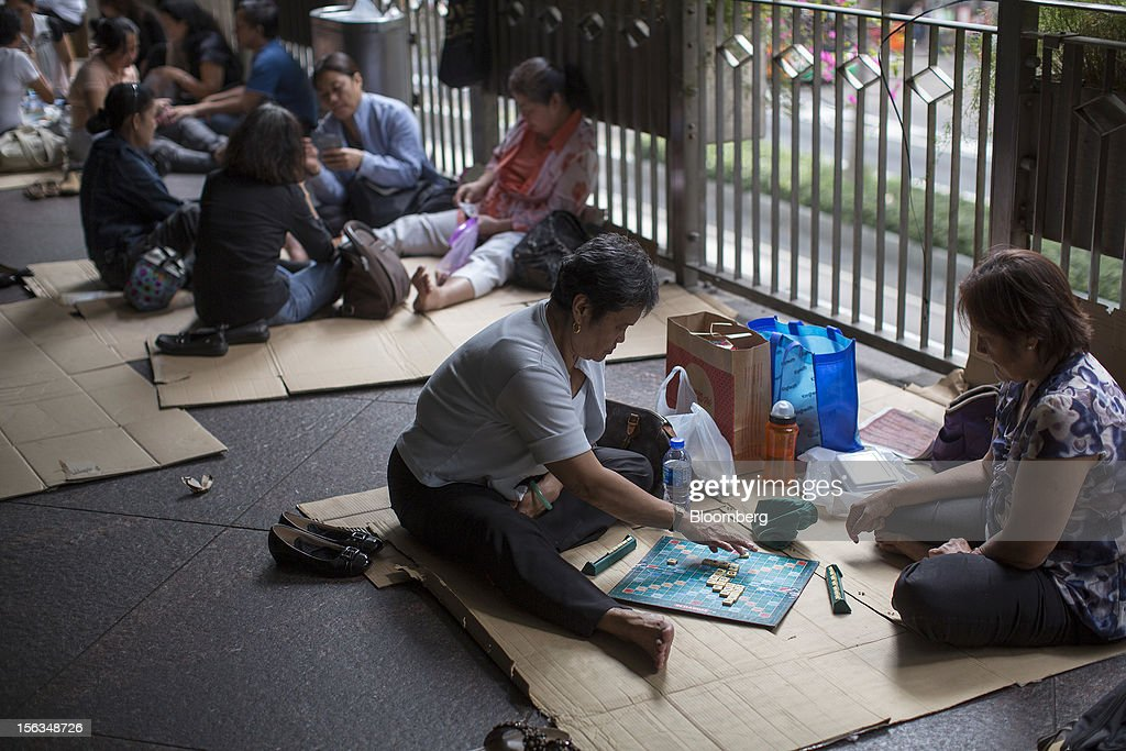 Migrant workers play games on their day off in the Central district of Hong Kong, China, on Sunday, Nov. 11, 2012. Hong Kong's more than 300,000 domestic workers cook, clean and take care of children and the elderly. Photographer: Jerome Favre/Bloomberg via Getty Images