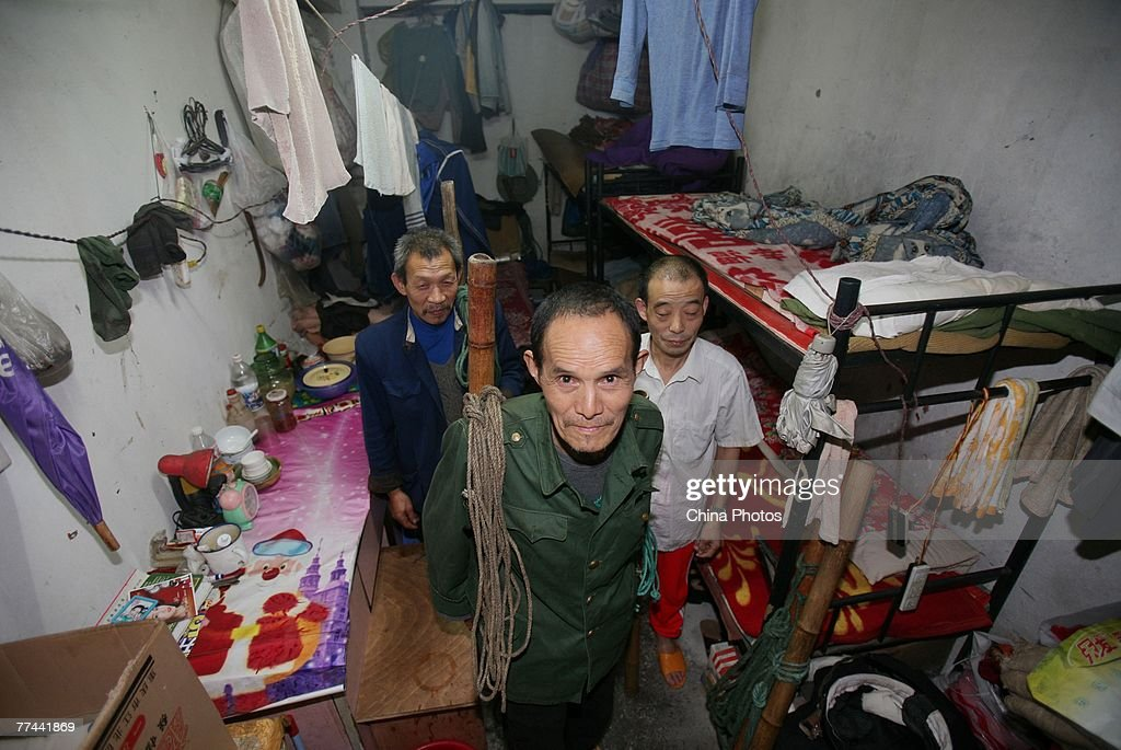 Migrant workers pose in their room at the Yangguang Apartment also known as 'Bangbang Apartment' as most of its residents are 'Bangbangs' traditional...