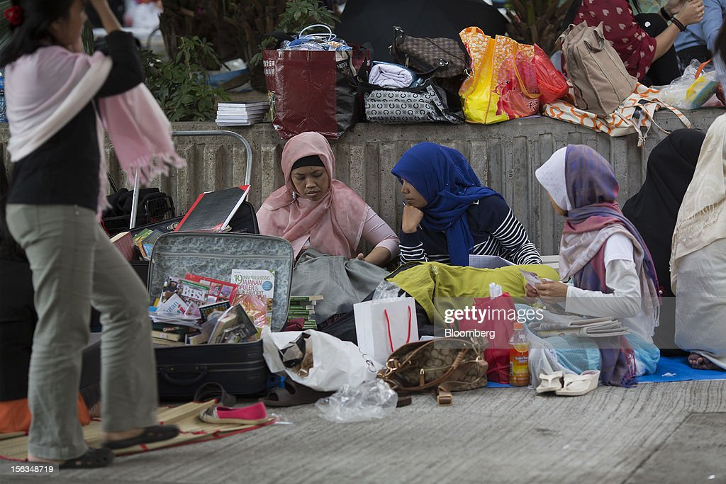 Migrant workers sit in Victoria Park on their day off in Hong Kong, China, on Sunday, Nov. 11, 2012. Hong Kong's more than 300,000 domestic workers cook, clean and take care of children and the elderly. Photographer: Jerome Favre/Bloomberg via Getty Images