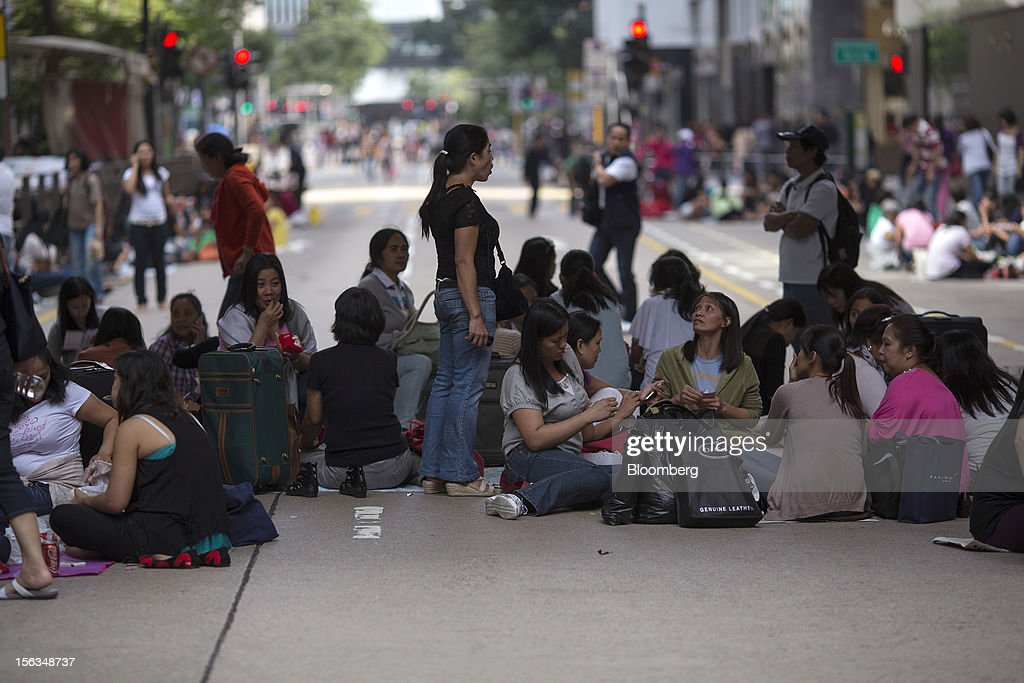 Migrant workers sit on Chater Road on their day off in the Central district of Hong Kong, China, on Sunday, Nov. 11, 2012. Hong Kong's more than 300,000 domestic workers cook, clean and take care of children and the elderly. Photographer: Jerome Favre/Bloomberg via Getty Images