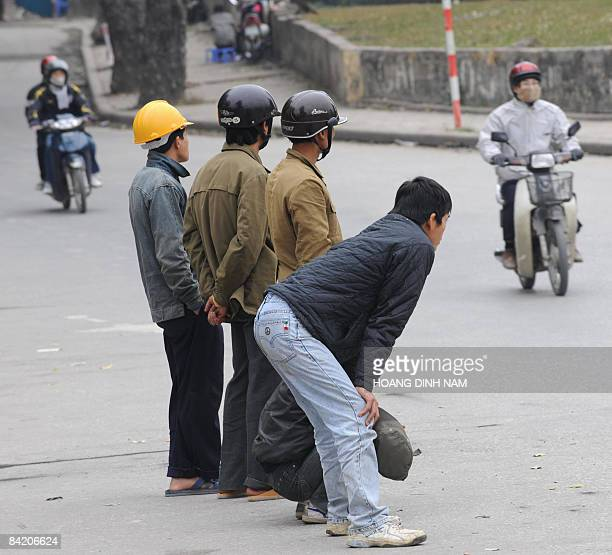 Migrant workers stand looking for daily jobs on a Hanoi street on January 8 2009 Experts and official media predict that up to 300000 workers could...