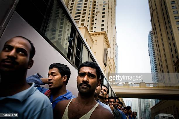 Migrant workers wait in line for a bus to return them to the labor camps located outside the city after a day of work July 9 2008 in Dubai United...
