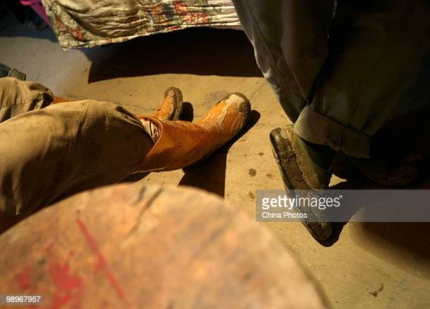 Migrant workers wearing muddy boots rest in a shipping container house at the south bank of the Minjiang River on May 11 2010 in Fuzhou of Fujian...
