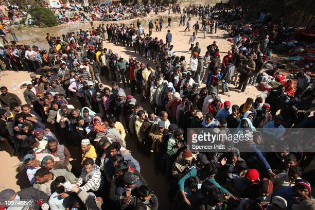 Migrant workers who recently crossed into Tunisia from Libya lineup to receive food and water at a temporary camp on March 03 2011 in Ras Jdir...