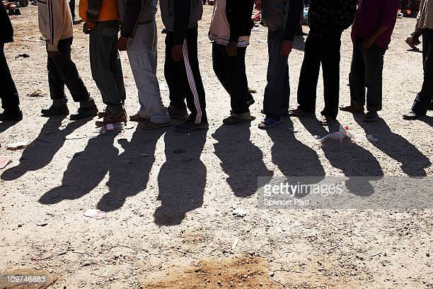 Migrant workers who recently crossed into Tunisia from Libya wait to receive food and water at a temporary camp on March 03 2011 in Ras Jdir Tunisia...