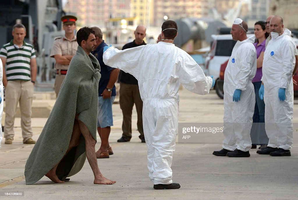 A migrant (L) wrapped in a banket arrives at Hay Wharf in Valletta after being rescued by a patrol boat of the Armed forces of Malta on October 12, 2013, a day after a boat carrying migrants sank. More than 140 survivors, plucked from the sea after their overloaded boat sank in the latest deadly migrant tragedy to hit the Mediterranean, arrived in Malta. The sinking killed more than 30, most of them women and children, when the boat packed with people desperate to reach European shores went down off Malta near the Italian island of Lampedusa, according to officials. AFP PHOTO/MATTHEW MIRABELLI