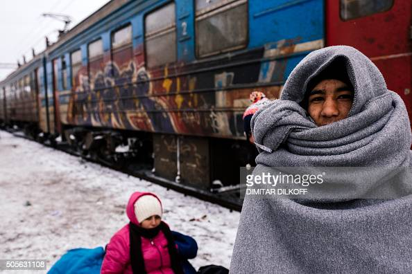 A migrant wrapped in a blanket to keep warm waits to catch a train heading to the border with Croatia at the train station of Presevo on January 19...