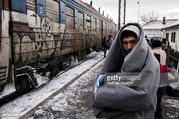 TOPSHOT A migrant wrapped in a blanket to keep warm waits with other migrants and refugees to board a train heading to the border with Croatia at the...