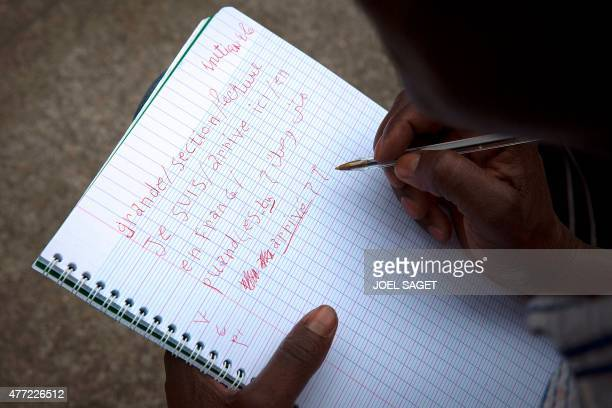 A migrant writes on a notebook during a French lesson organised by volunteers in a camp located next to the Austerlitz station in Paris on June 14...