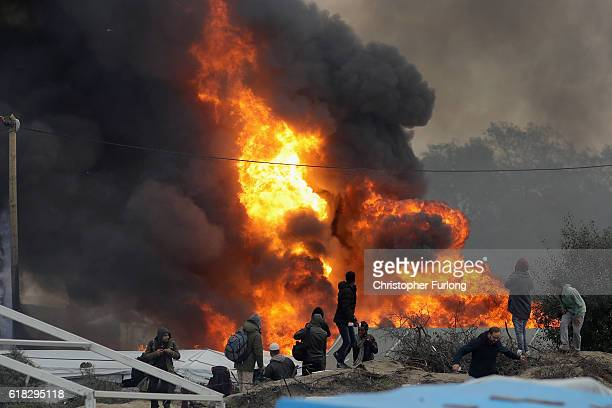 Migrants and media look on as a gas canister explodes in the Jungle camp as fires rage believed to have been started by departing migrants as...