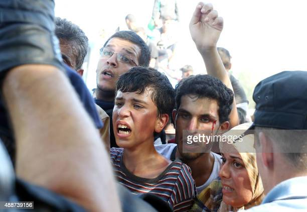 Migrants and refugees are stopped in front of a police cordon on they way to board buses at the train station in the city of Tovarnik close to the...