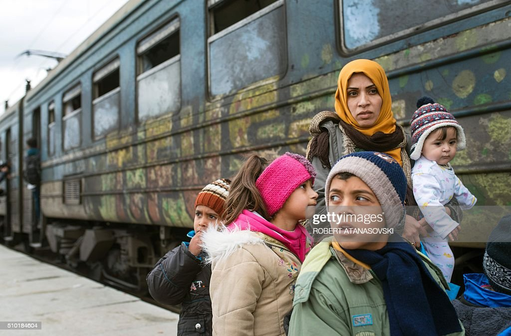Migrants and refugees board a train heading to Serbia from the Macedonian-Greek border near Gevgelija on February 14, 2016. Dutch Foreign minister Bert Koenders today spent an hour in a Vinojug recipient center near Gevgelija talking with migrants, children, UNICEF and Red Cross representatives, police and others members that are taking care of migrants that are heading to the EU from devastated homes in Syria, Afghanistan and Iraq. / AFP / Robert ATANASOVSKI