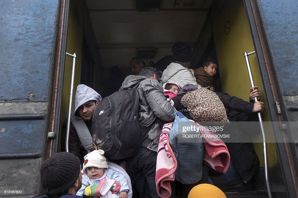 Migrants and refugees board a train heading to Serbia from the Macedonian-Greek border near Gevgelija on February 14, 2016. Dutch Foreign minister Bert Koenders on February 14 spent an hour in a Vinojug recipient center near Gevgelija talking with migrants, children, UNICEF and Red Cross representatives, police and others members that are taking care of migrants that are heading to the EU from devastated homes in Syria, Afghanistan and Iraq. / AFP / Robert ATANASOVSKI