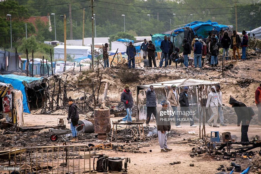 Migrants and refugees clear up the wreckage of burnt-out shelters at the 'Jungle' migrant camp in the northern French town of Calais on May 27, 2016 a day after after a massive brawl that left 40 people injured. Some 20 people living in the 'Jungle' refugee camp in the northern French port of Calais were injured in a brawl between around 200 Afghans and Sudanese on May 26, 2016. / AFP / PHILIPPE