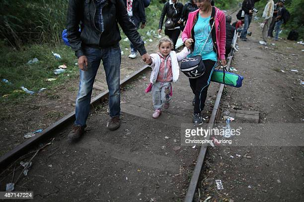 Migrants and refugees cross the border from Serbia into Hungary along the railway tracks close to the village of Roszke on September 6 2015 in Szeged...