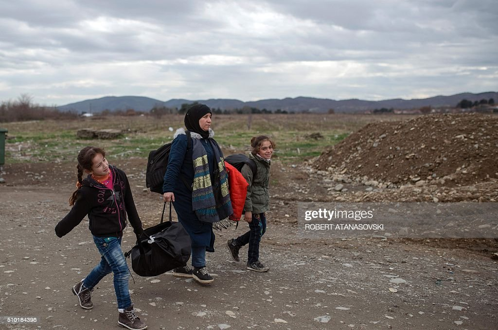 Migrants and refugees cross the Greek-Macedonian border near the town of Gevgelija, on February 14, 2016. Dutch Foreign minister Bert Koenders today spent an hour in a Vinojug recipient center near Gevgelija talking with migrants, children, UNICEF and Red Cross representatives, police and others members that are taking care of migrants that are heading to the EU from devastated homes in Syria, Afghanistan and Iraq. / AFP / Robert ATANASOVSKI