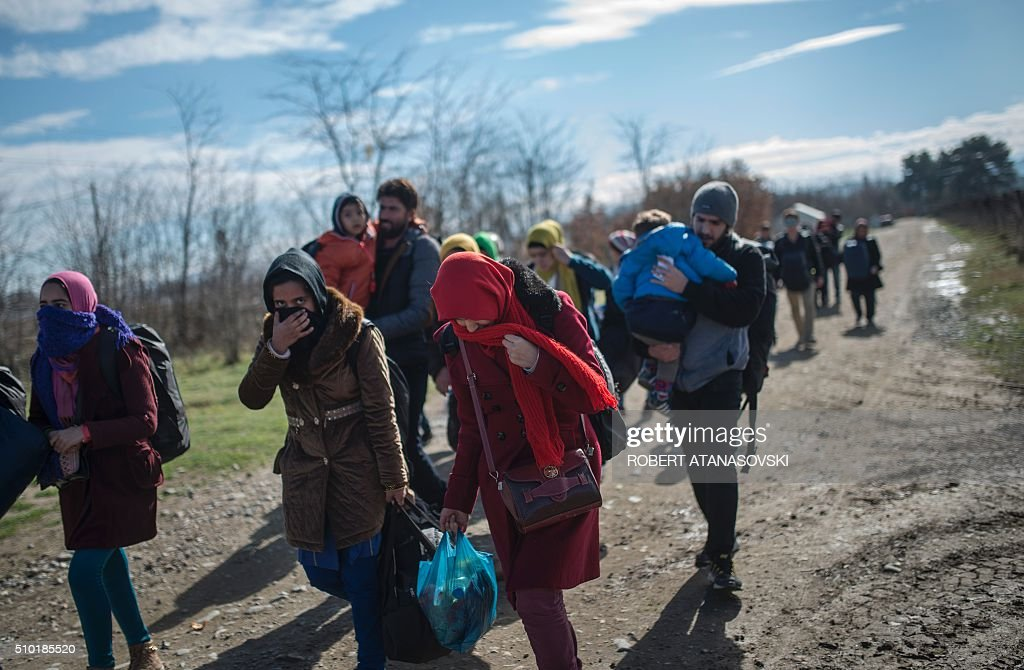 Migrants and refugees cross the Greek-Macedonian border near the town of Gevgelija, on February 14, 2016. The Central African Republic holds delayed presidential and parliamentary polls on February 14, with voters desperate to usher in peace after the country's worst sectarian violence since independence in 1960. / AFP / Robert ATANASOVSKI