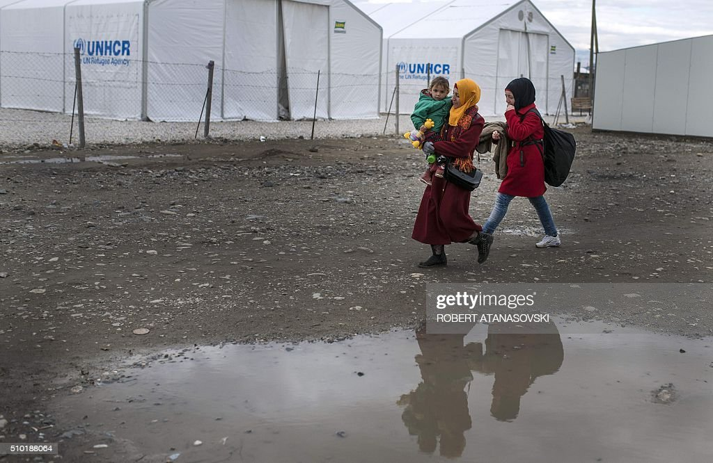 Migrants and refugees cross the Greek-Macedonian border near the town of Gevgelija, on February 14, 2016. Dutch Foreign minister Bert Koenders on February 14 spent an hour in a Vinojug recipient center near Gevgelija talking with migrants, children, UNICEF and Red Cross representatives, police and others members that are taking care of migrants that are heading to the EU from devastated homes in Syria, Afghanistan and Iraq. / AFP / Robert ATANASOVSKI
