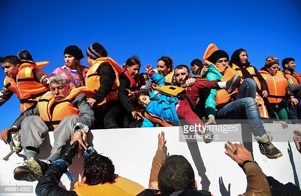 Migrants and refugees disembark from a boat as they arrive on the Greek island of Lesbos after crossing the Aegean Sea from Turkey on November 26...