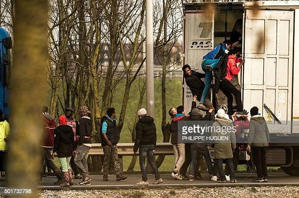 TOPSHOT Migrants and refugees enter the trailer of a truck on December 17 2015 on the site of the Eurotunnel in Calais A growing number of migrants...