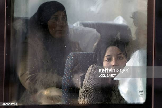 Migrants and refugees families mainly from Syrian sit in a bus after being removed from their make shift camp by the French authorities setup at the...