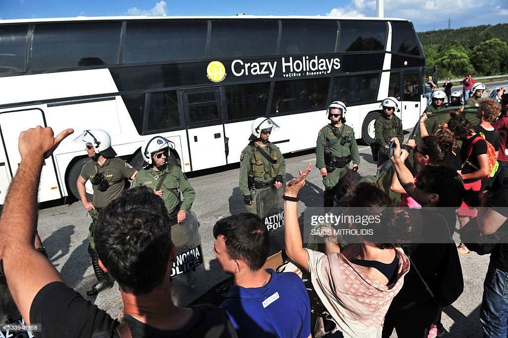 Migrants and refugees leave by bus as solidarity groups protest behind a line of riot police during the forced evacuation of a makeshift camp close to the Greece-Macedonia border, near the village of Idomeni on May 24, 2016. Greek police on May 24 moved hundreds of migrants out of the overcrowded camp of Idomeni, launching a major operation to clear up the squalid tent city where thousands fleeing war and poverty had lived for months. In an operation that began shortly after sunrise, Greek police said they had put more than 1,500 people on buses to newly opened camps near Greece's second city Thessaloniki, about 80 kilometres (50 miles) to the south. MITROLIDIS