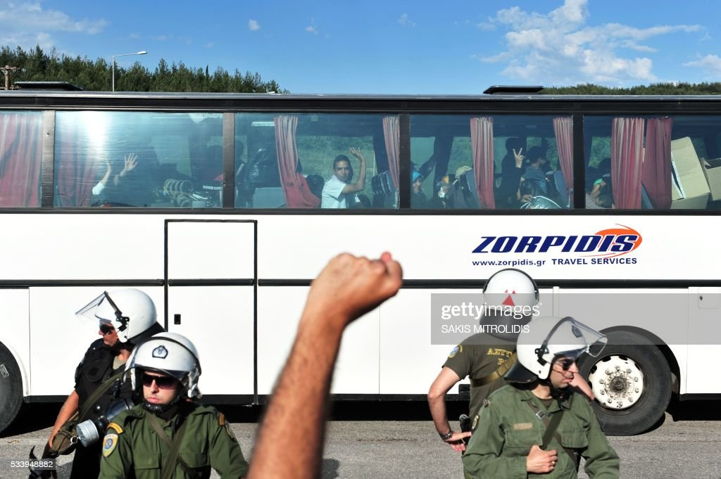 Migrants and refugees leave by bus as solidarity groups protest behind riot police during the forced evacuation of a makeshift camp close to the Greece-Macedonia border, near the village of Idomeni on May 24, 2016. Greek police on May 24 moved hundreds of migrants out of the overcrowded camp of Idomeni, launching a major operation to clear up the squalid tent city where thousands fleeing war and poverty had lived for months. In an operation that began shortly after sunrise, Greek police said they had put more than 1,500 people on buses to newly opened camps near Greece's second city Thessaloniki, about 80 kilometres (50 miles) to the south. MITROLIDIS