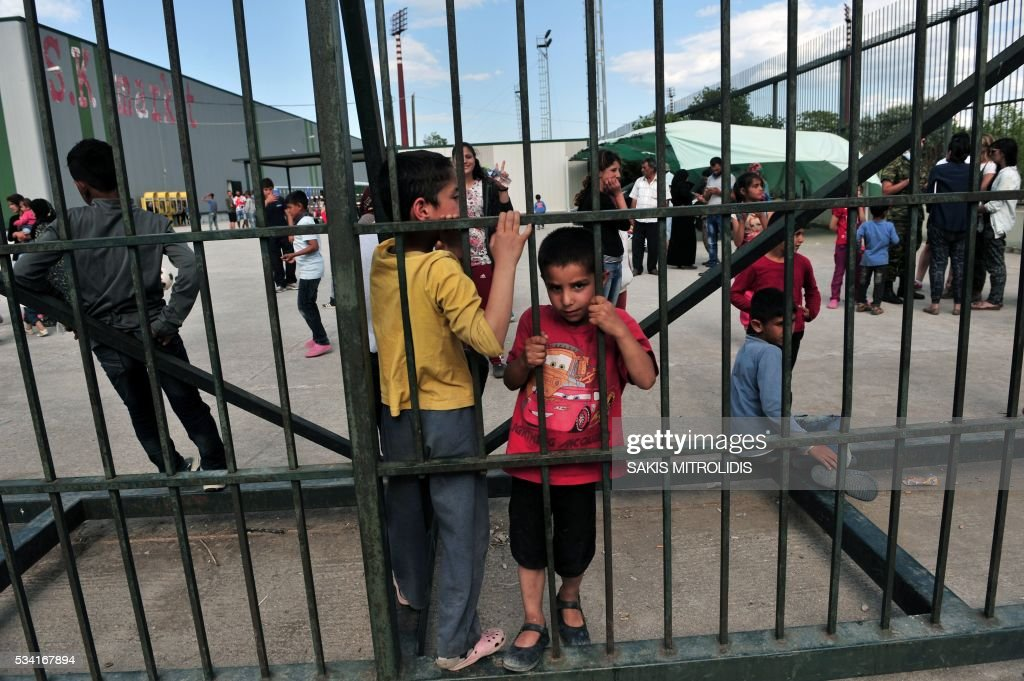 Migrants and refugees look on within the Kalohori refugee camp on May 25, 2016, near Thessaloniki. Greek police on May 25 moved hundreds more migrants out of Idomeni, the squalid tent city where thousands fleeing war and poverty have lived for months, on the second day of an operation likely to last a week. Some 600 people were bussed away from the camp on the Macedonian border to newly opened camps near Greece's second city Thessaloniki, about 80 kilometres (50 miles) south, bringing the total moved out to 2,600 since May 24. MITROLIDIS