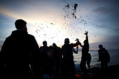 Migrants and refugees mainly from Afghanistan and Syria perform a dance of joy after arriving on an inflatable boat with other refugees crossing the...