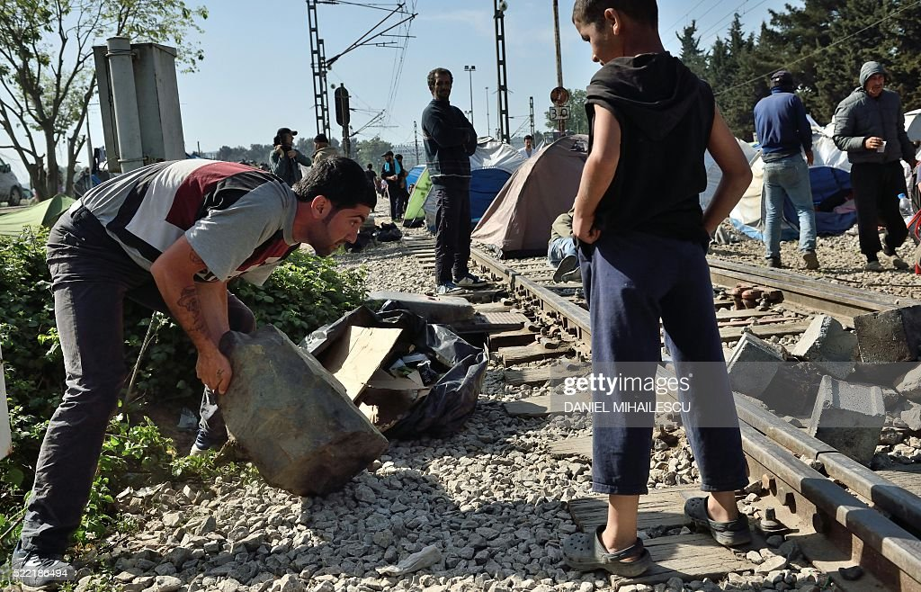 Migrants and refugees move a boulder on the train tracks in sign of protest as Greek police try to convince them to leave the railroad in the makeshift camp at the Greek-Macedonian border near the village of Idomeni, on April 18, 2016. According to statistics released on on April 8 by the International Organization of Migrants (IOM), more than 152,000 people have arrived in Greece by sea from Turkey since January 1, nearly three-quarters of whom were Syrians. / AFP / DANIEL