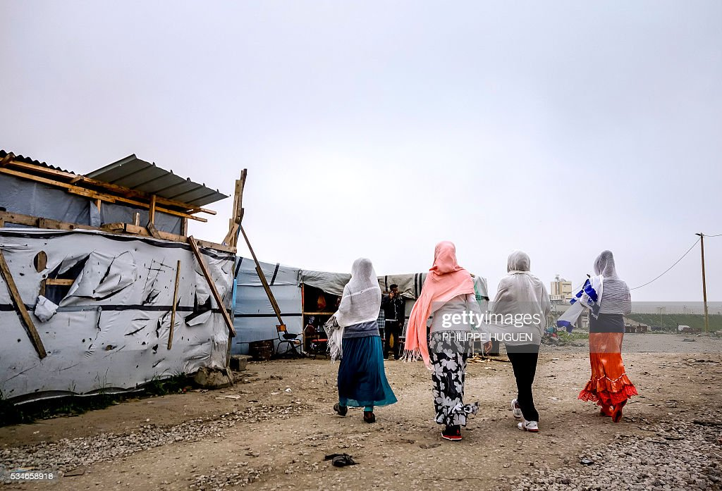 Migrants and refugees of Eritrean origin walk amongst shelters at the 'New Jungle' migrant camp in the northern French town of Calais on May 27, 2016 a day after after a massive brawl between migrant factions that left 40 people injured. Some 20 people living in the 'Jungle' refugee camp in the northern French port of Calais were injured in a brawl between around 200 Afghans and Sudanese on May 26, 2016. / AFP / PHILIPPE