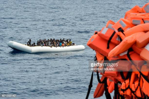 Migrants and refugees on a rubber boat wait to be evacuated during a rescue operation by the crew of the Topaz Responder a rescue ship run by Maltese...
