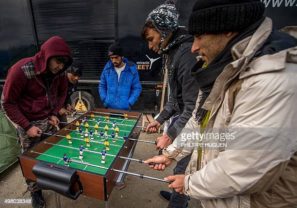 Migrants and refugees play table football in the migrant camp known as the 'Jungle' near the northern French port of Calais on November 20 2015 where...
