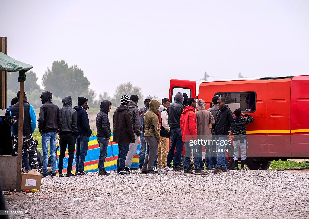 Migrants and refugees queue up to receive a meal at the 'New Jungle' migrant camp in the northern French town of Calais on May 27, 2016 a day after after a massive brawl between migrant factions that left 40 people injured. Some 20 people living in the 'Jungle' refugee camp in the northern French port of Calais were injured in a brawl between around 200 Afghans and Sudanese on May 26, 2016. / AFP / PHILIPPE