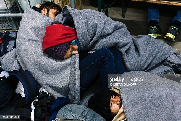 Migrants and refugees rest on January 20 2016 at a registration camp in southern Serbian town of Presevo after crossing the Macedonian border as...