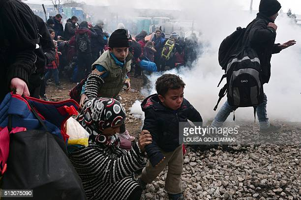 Migrants and refugees run away after Macedonian police fired tear gas at hundreds of Iraqi and Syrian migrants who tried to break through the Greek...