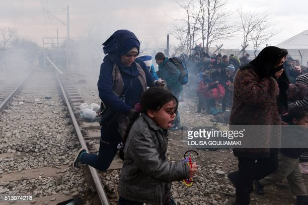TOPSHOT Migrants and refugees run away from teargas and stun grenades after Macedonian police fired tear gas at hundreds of Iraqi and Syrian migrants...