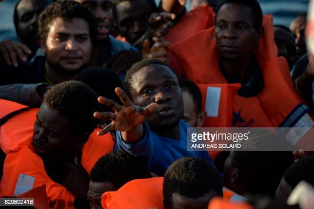 TOPSHOT Migrants and refugees seated on a rubber boat grab life jackets thrown by members of the crew of the Topaz Responder rescue ship run by...