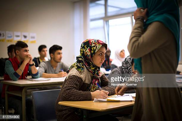 Migrants and refugees seeking asylum in Germany attend a Germanlanguage class at the shelter where they live while their asylum applications are...