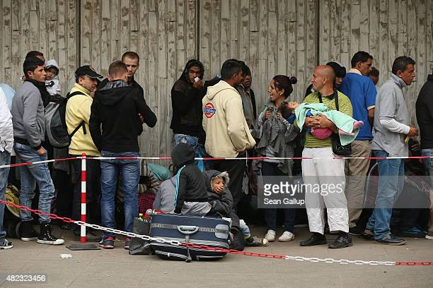 Migrants and refugees seeking asylum in Germany wait outside the Central Registration Office for Asylum Seekers of the State Office for Health and...