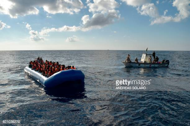 TOPSHOT Migrants and refugees sit on a rubber boat as the Libyan coastguards patrol during a rescue operation of the Topaz Responder a rescue ship...