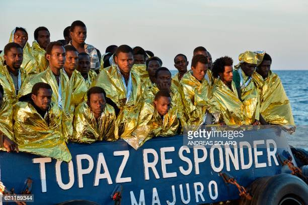 Migrants and refugees stand aboard the Topaz Responder ship run by Maltese NGO Moas and the Italian Red Cross during a rescue operation on November 5...