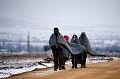 Migrants and refugees use their sleeping blankets to keep warm as they walk along snowcovered fields after crossing the MacedonianSerbian border near...