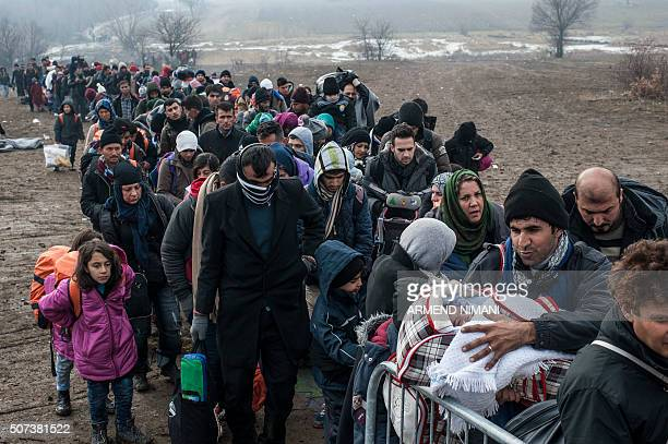 TOPSHOT Migrants and refugees wait for security check after crossing the Macedonian border into Serbia near the village of Miratovac on January 29...