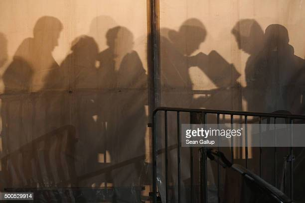 Migrants and refugees wait in the early hours in a tent outside the Central Registration Office for Asylum Seekers of the State Office for Health and...