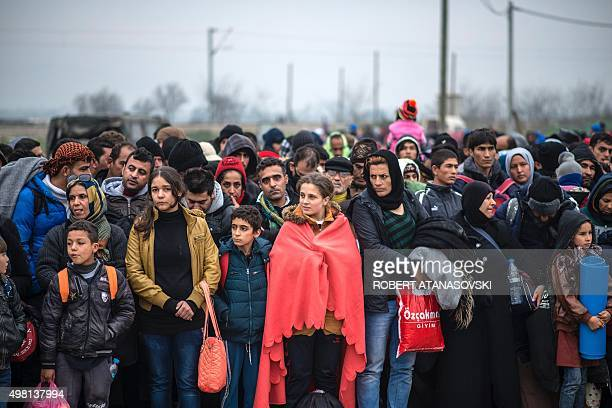 Migrants and refugees wait outside a registration camp after crossing the GreekMacedonian border near Gevgelija on November 21 2015 Serbia and...