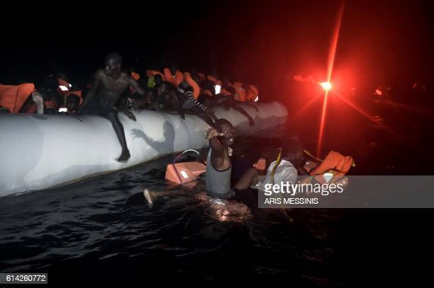 TOPSHOT Migrants and refugees wait to be rescued from their sinking rubber boat some eight nautical miles off Libya's Mediterranean coastline on...