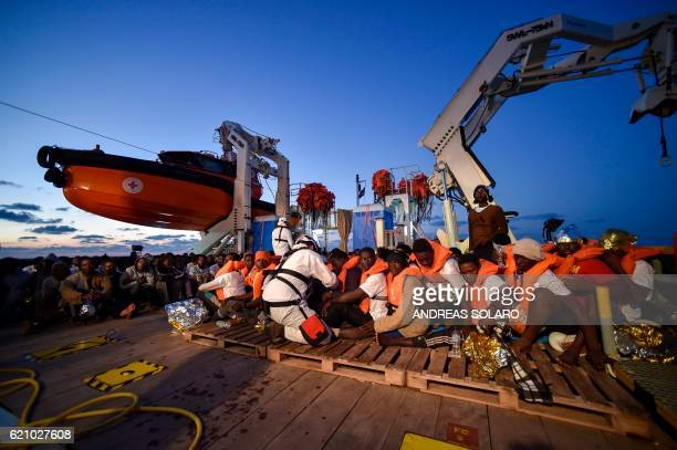 TOPSHOT Migrants and refugees wait to be trasferred from the Topaz Responder ship run by Maltese NGO 'Moas' and the Italian Red Cross to the Vos...