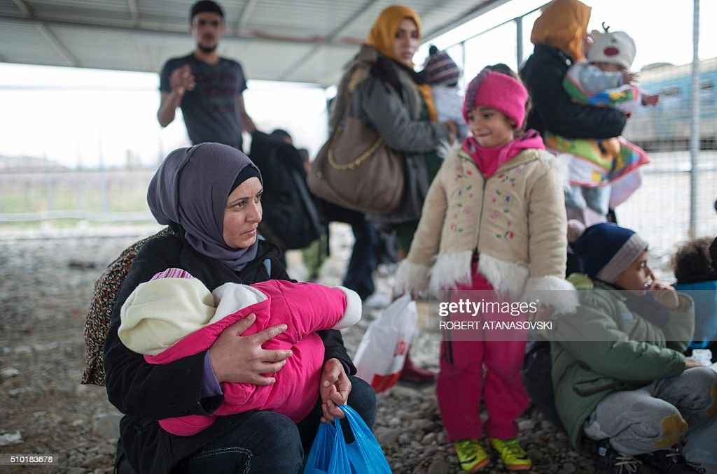 Migrants and refugees wait to board a train heading to Serbia from the Macedonian-Greek border near Gevgelija on February 14, 2016. Dutch Foreign minister Bert Koenders today spent an hour in a Vinojug recipient center near Gevgelija talking with migrants, children, UNICEF and Red Cross representatives, police and others members that are taking care of migrants that are heading to the EU from devastated homes in Syria, Afghanistan and Iraq. / AFP / Robert ATANASOVSKI