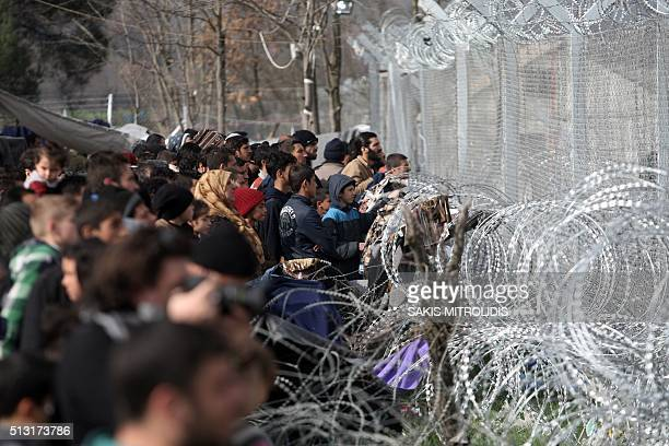 Migrants and refugees wait to cross the GreeceMacedonia border near the village of Idomeni on 1 March 2016 Macedonian police fired tear gas as some...